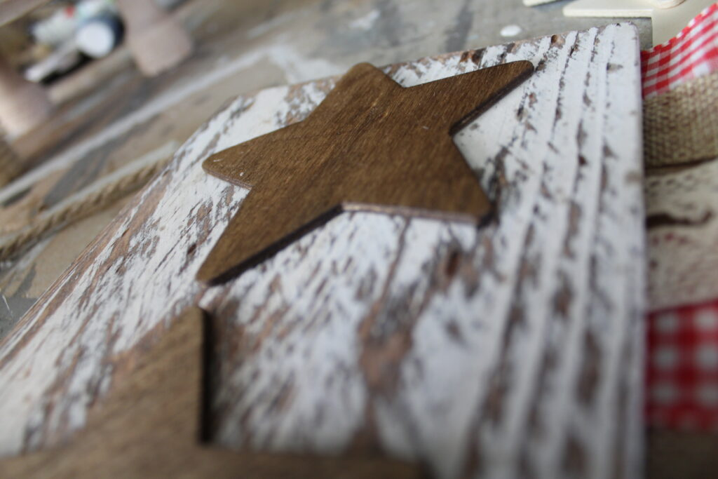 stain star cutouts on a distressed white plank