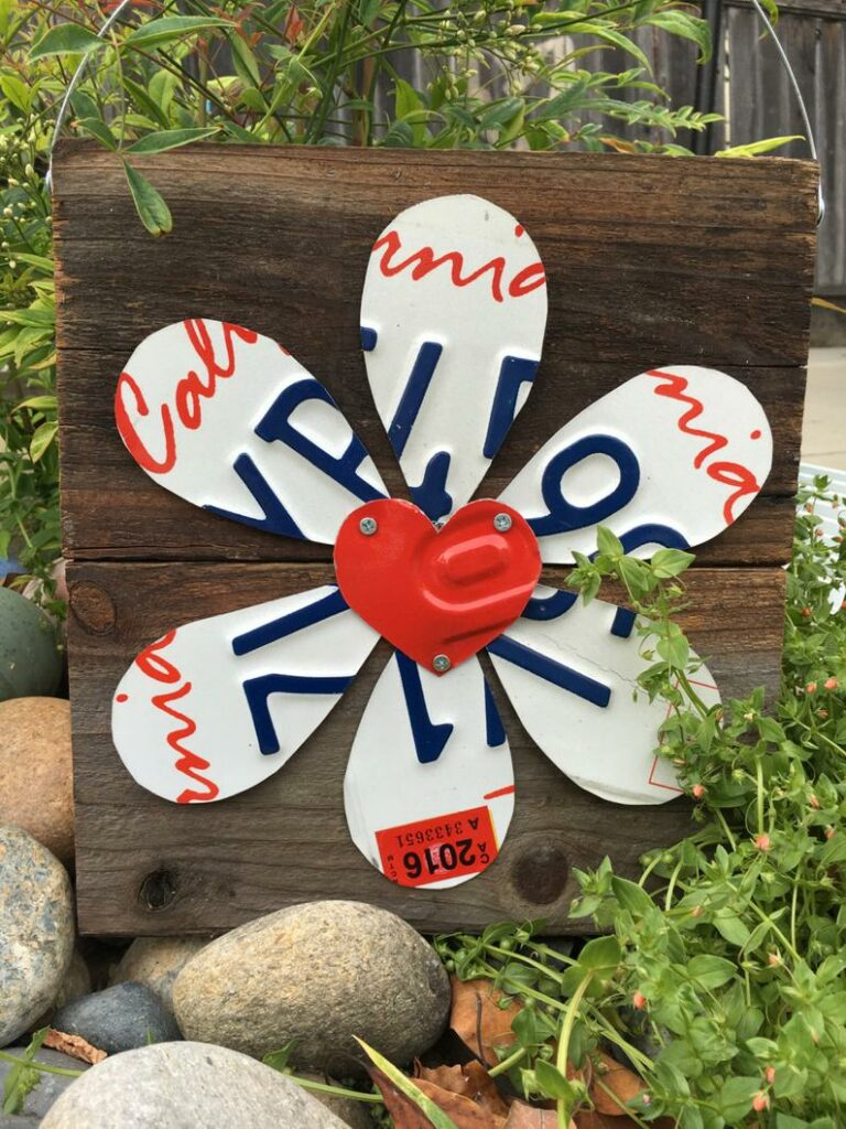 flower cute out of a license plate attahed to an old piece of barnwood with metal hanger and red heart in the center