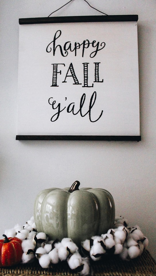 green pumpkin with cotton stems and scrap wood sign