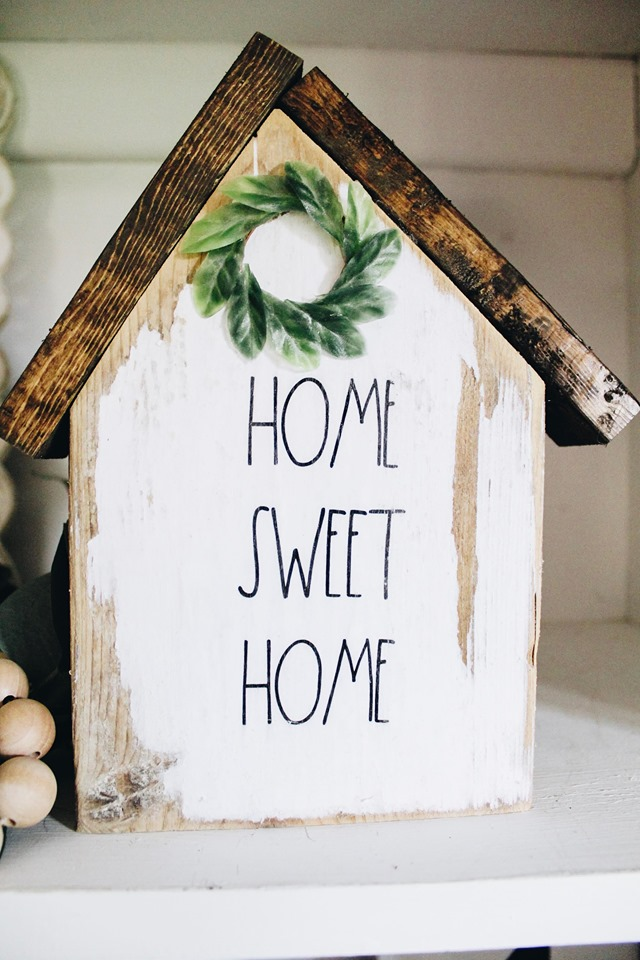 small wood block house with words home sweet home written on it and a mini magnolia wreath at the pitch of the roof