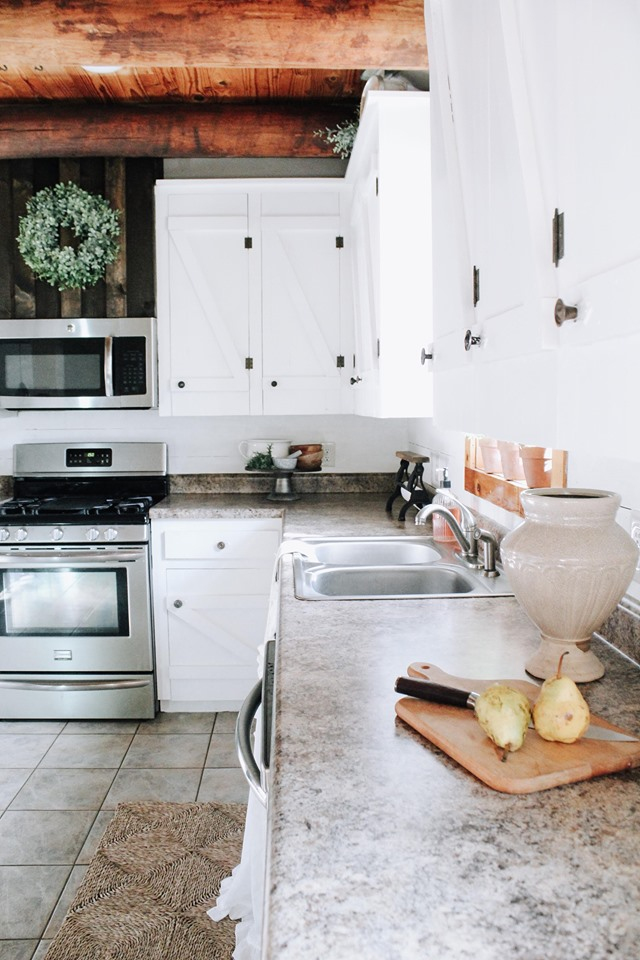 white farmhouse kitchen with board and batton cabinets and a dark wood vent hood made from scrap wood. A cutting board on the countertop with a knife and two ripe pears