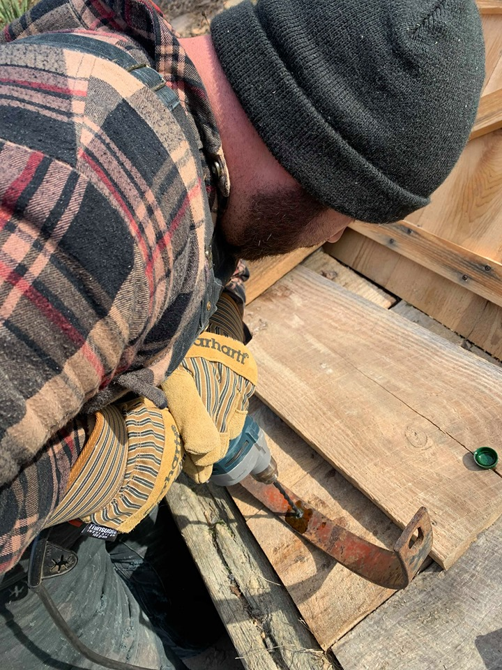 man drilling a hole into rusty metal for a upcycled kitchen island dresser