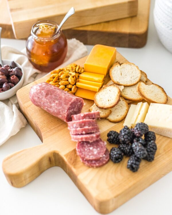 Beautiful scrap wood cutting board with meats and cheeses served on top