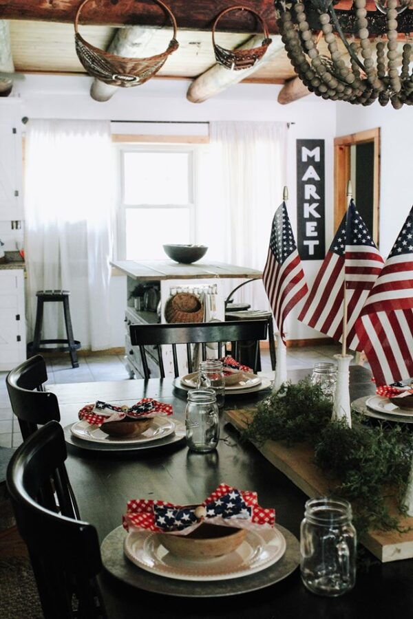 RED WHITE AND BLUE NAPKIN ON FARMHOUSE TABLE SCAPE WOITH FLAGS IN GLASS MILK VASES