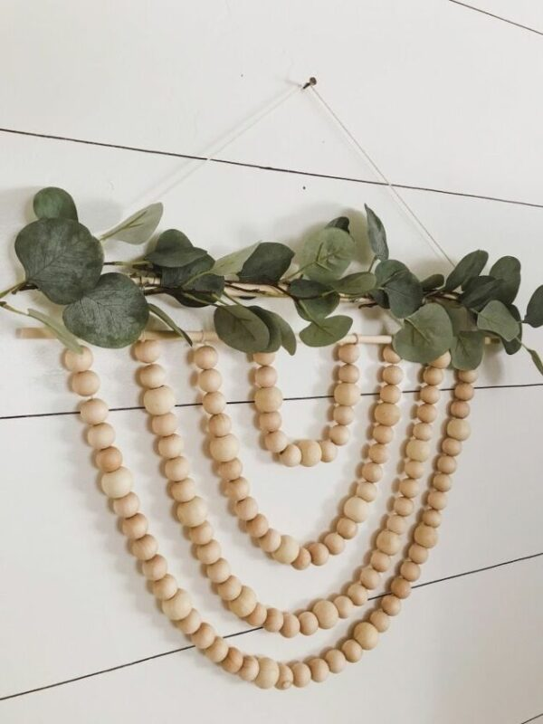 wood bead garland stranding hanging from a dowel rod with greenery