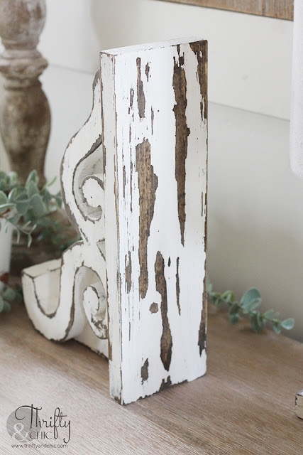 Beautiful scrap wood corbel chippy white paint sitting on a shelf with greenery