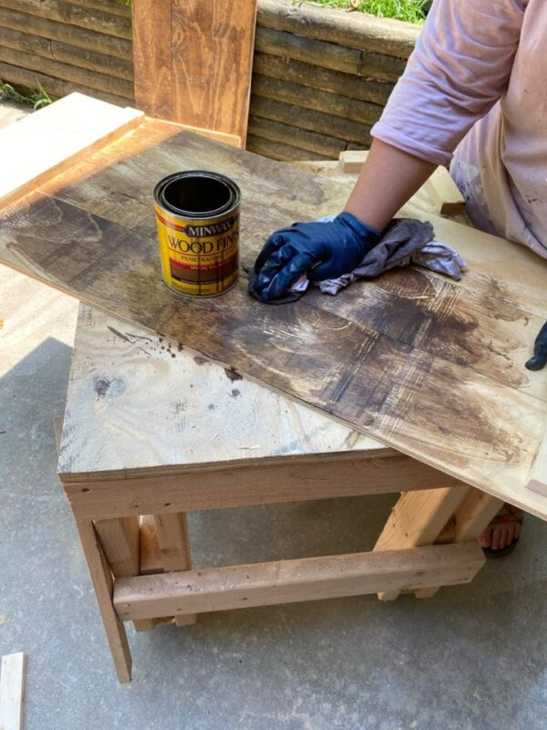 minwax stain being applied to plywood planks with glove and rag
