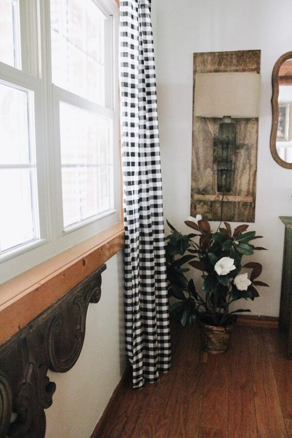 window with magnolia plant in the floor and buffalo check curtain