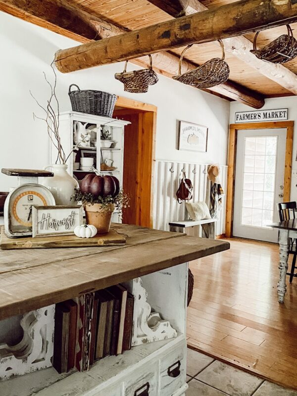 rustic country kitchen island with old books on lower shelv and pumpkin rustic vignette