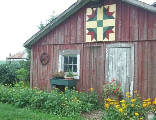 red rustic barn with colorful quilt