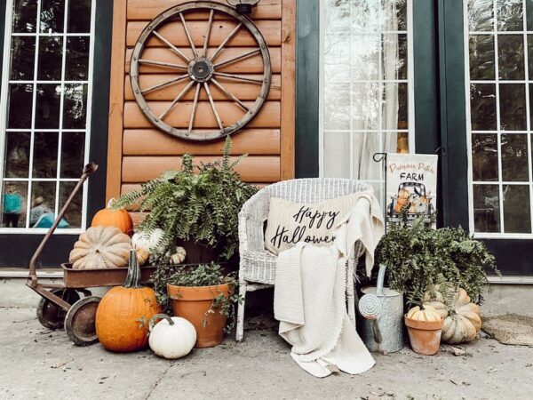 antique wicker chair with pumpkins and ferns in front of log cabin