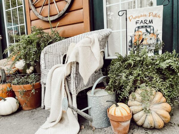 ferns and pumpkins with old white wicker chair