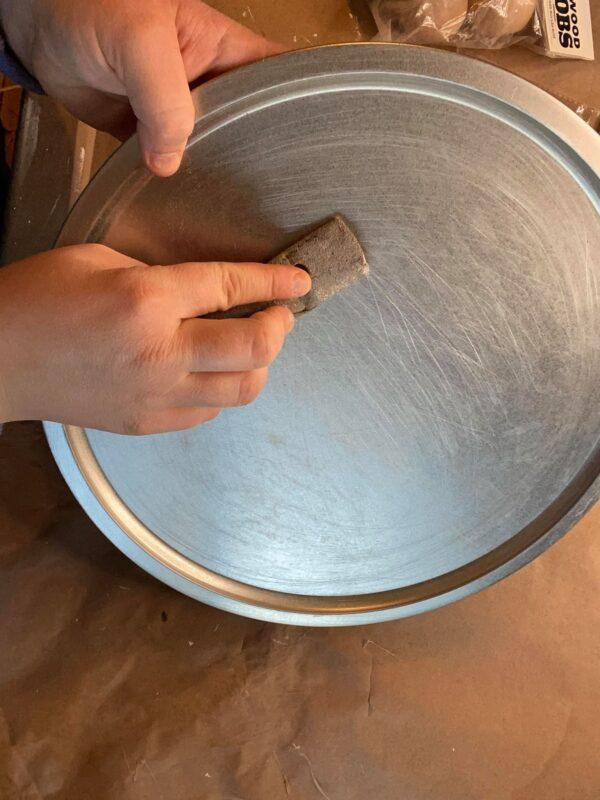sand a dollar tree pizza pan to make a farmhouse riser