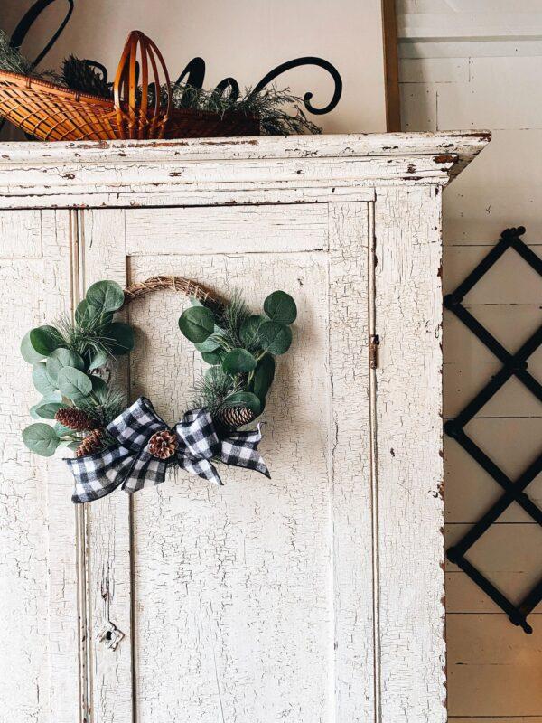 rustic winter wreath on chippy farmhouse cabinet