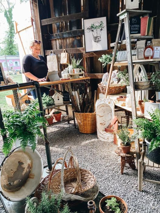The Home Good Market set up shop inside of old rustic barn. Hand Picked, Unique Items are displayed on weathered wood, mixed with antiques.