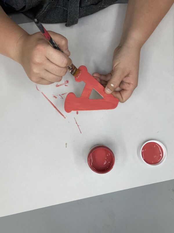painting a wooden letter red