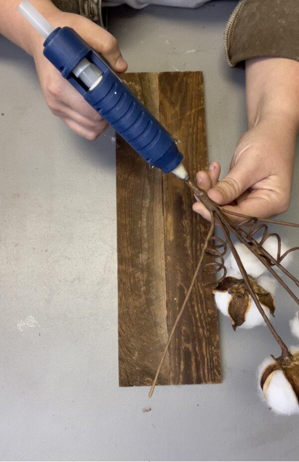hot glue cotton stem to scrap barn wood